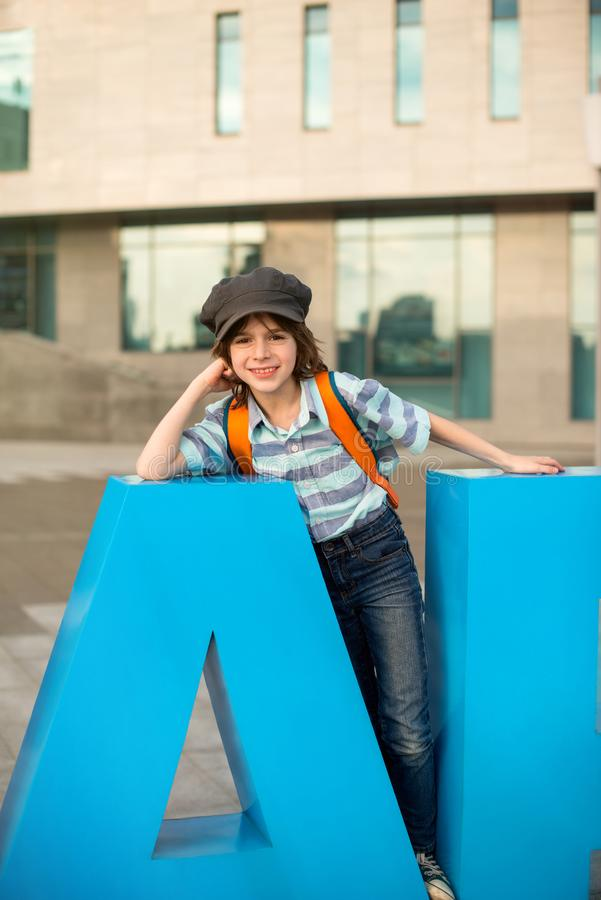 Emotional portrait of a schoolboy with a knapsack behind his back and in a cap. He stands by the high-rise building on the city. Square, leaning on a small royalty free stock photo