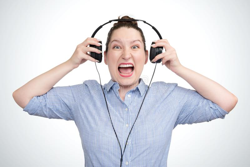 Emotional portrait young girl listening aggressive music in headphones stock photo