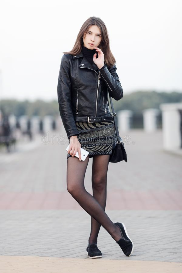 Emotional portrait of a young pretty brunette woman posing full length outdoors city park wearing black leather coat holding smart royalty free stock photo