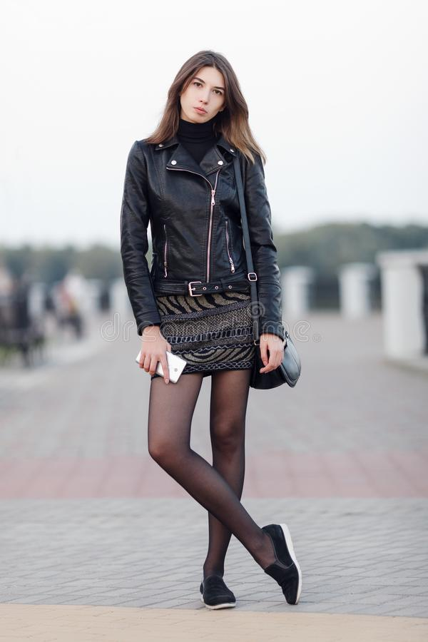 Emotional portrait of a young pretty brunette woman posing full length outdoors city park wearing black leather coat holding smart royalty free stock images