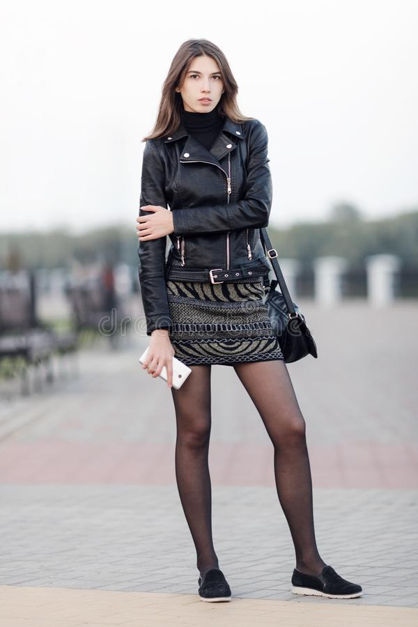 Emotional portrait of a young pretty brunette woman posing full length outdoors city park wearing black leather coat holding smart royalty free stock photography