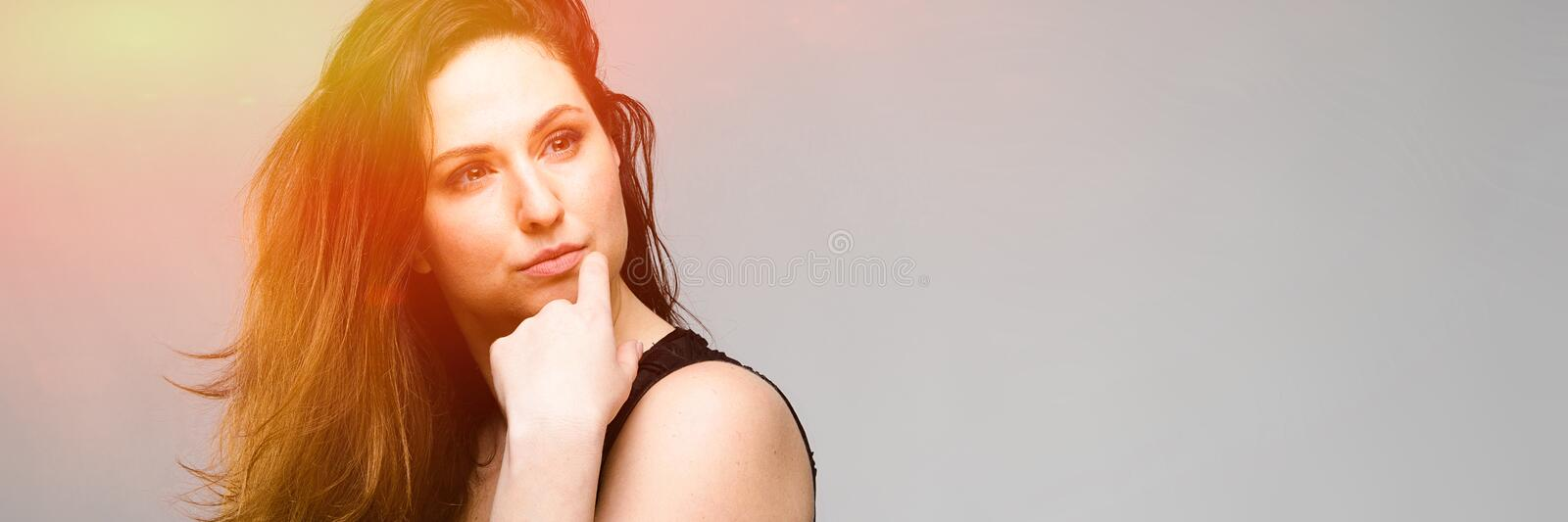 Emotional pretty confident cute plus size model standing in studio showing her beauty on gray background royalty free stock photo