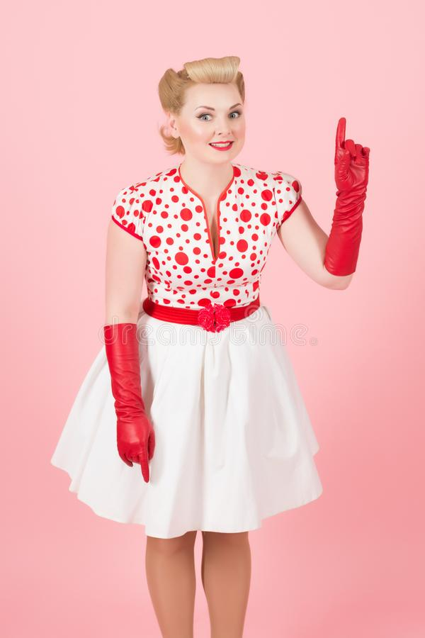 Cute lady in red gloves pointing her finger up and smiling royalty free stock images