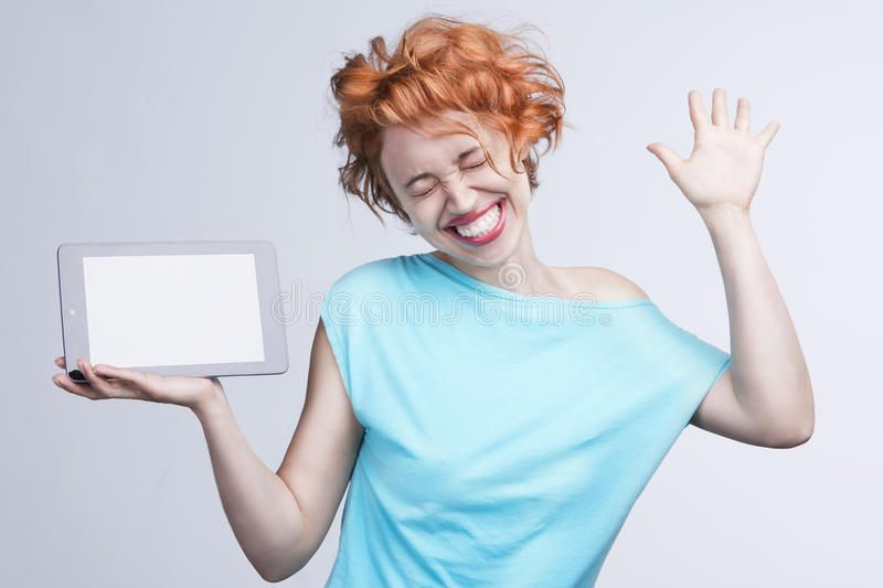 Emotional red-haired girl holding a tablet computer, dancing, jumping and laughing with delight. Empty space on the tablet pc, where you can place your text stock image