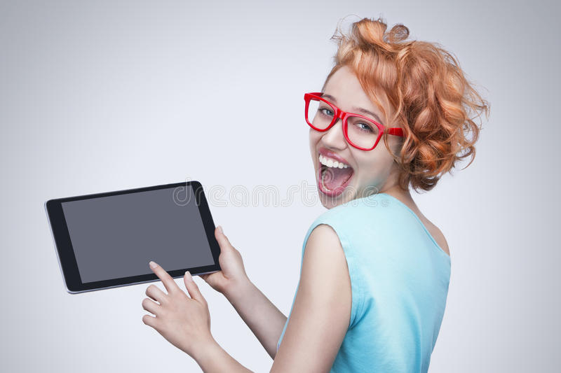 Emotional red-haired girl with red glasses holding and touching tablet computer. Bright beautiful attractive smile with teeth. Empty space on the tablet pc, you royalty free stock photos