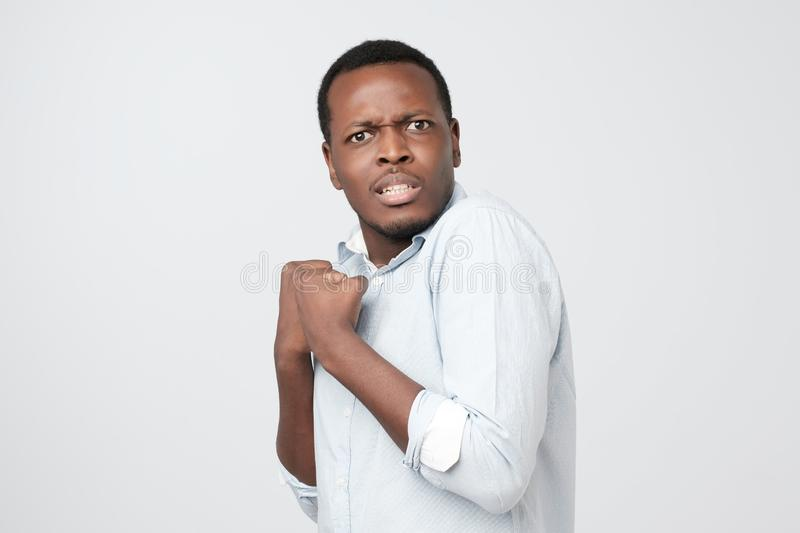 Emotional scared african male looking with frightened expression as sees something awful. stock photography