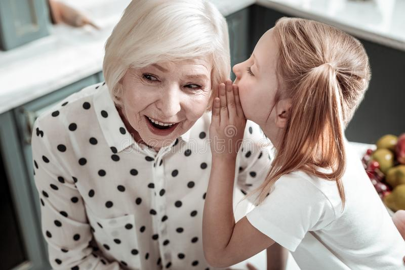 Emotional senior woman feeling impressed while granddaughter sharing secrets royalty free stock photography
