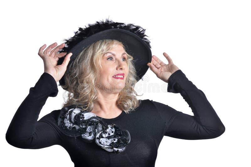 Emotional senior woman wearing black hat posing on white background stock image