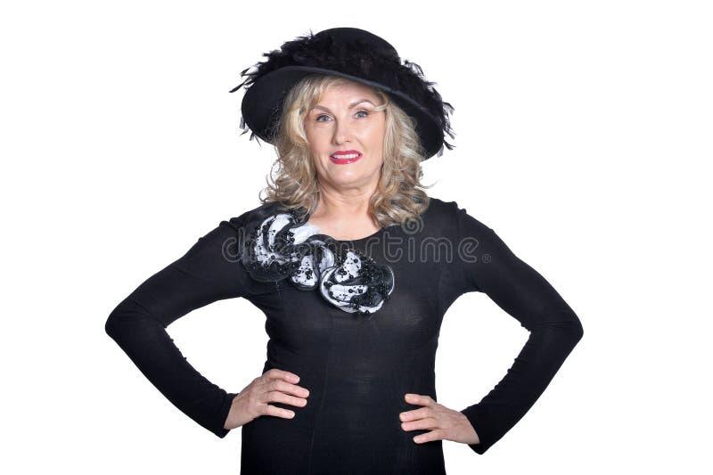 Emotional senior woman wearing black hat posing on white background stock photo