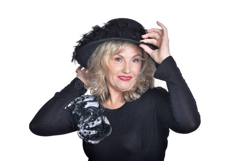 Emotional senior woman wearing black hat posing on white background royalty free stock photos