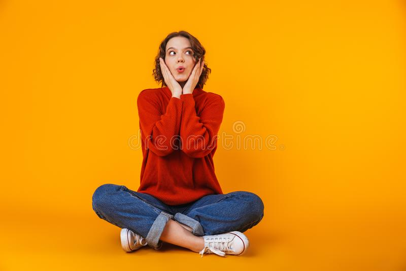 Emotional shocked young pretty woman posing  over yellow wall background stock photography
