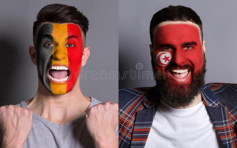Emotional soccer fans with painted flags on faces. Emotional soccer fans with painted Belgium and Tunisia flags on faces. Confrontation of football team royalty free stock image