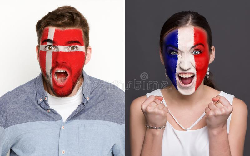 Emotional soccer fans with painted flags on faces. Emotional soccer fans with painted Denmark and France flags on faces. Confrontation of football team stock photography