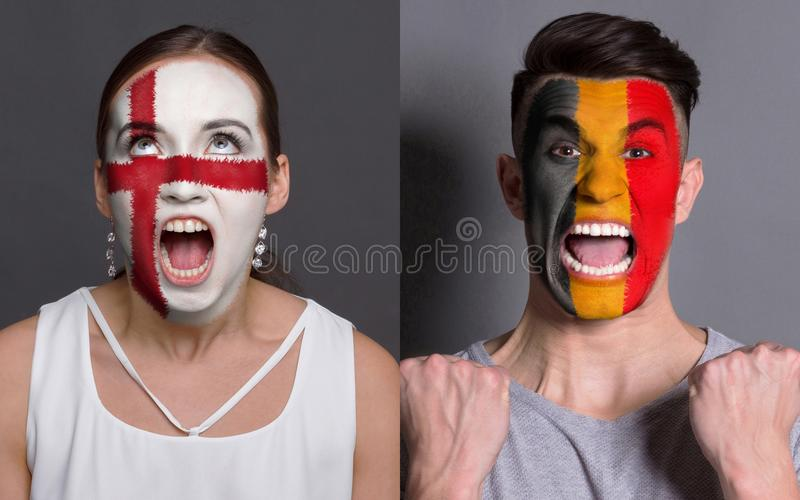 Emotional soccer fans with painted flags on faces. Emotional soccer fans with painted England and Belgium flags on faces. Confrontation of football team royalty free stock images