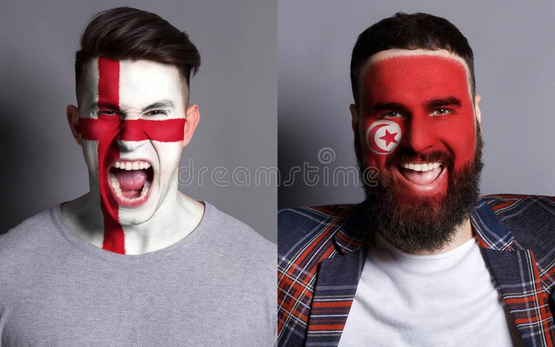 Emotional soccer fans with painted flags on faces. Emotional soccer fans with painted England and Tunisia flags on faces. Confrontation of football team royalty free stock photos