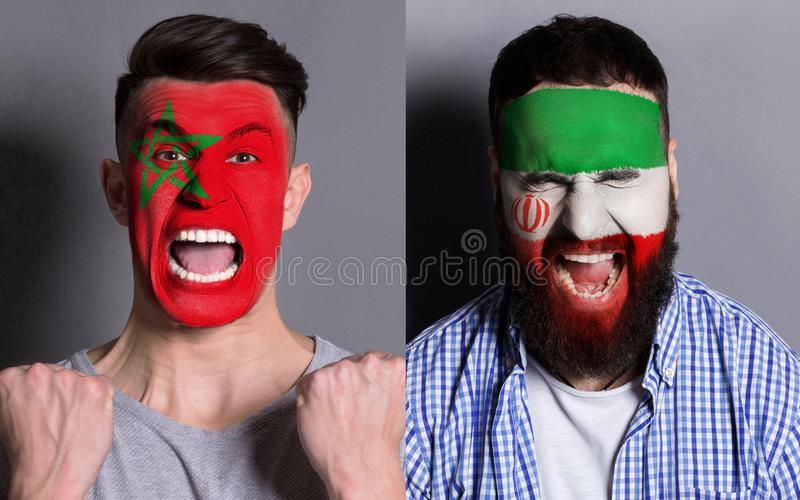 Emotional soccer fans with painted flags on faces. Emotional soccer fans with painted Morocco and Iran flags on faces. Confrontation of football team supporters royalty free stock photo