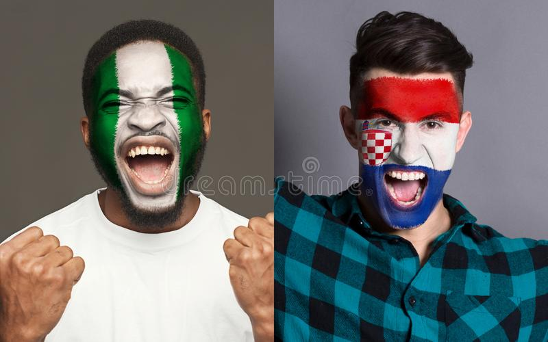 Emotional soccer fans with painted flags on faces. Emotional soccer fans with painted Nigeria and Croatia flags on faces. Confrontation of football team stock photo