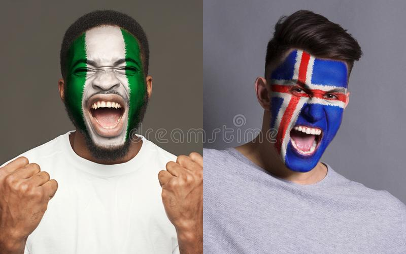 Emotional soccer fans with painted flags on faces. Emotional soccer fans with painted Nigeria and Iceland flags on faces. Confrontation of football team stock image