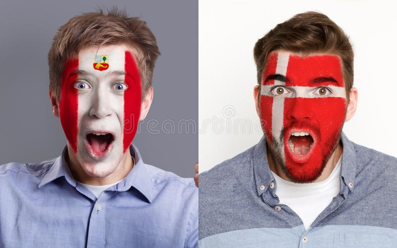 Emotional soccer fans with painted flags on faces. Emotional soccer fans with painted Peru and Denmark flags on faces. Confrontation of football team supporters stock photos