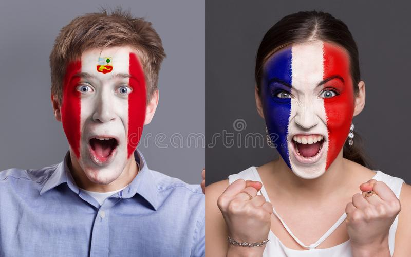 Emotional soccer fans with painted flags on faces. Emotional soccer fans with painted Peru and France flags on faces. Confrontation of football team supporters royalty free stock images