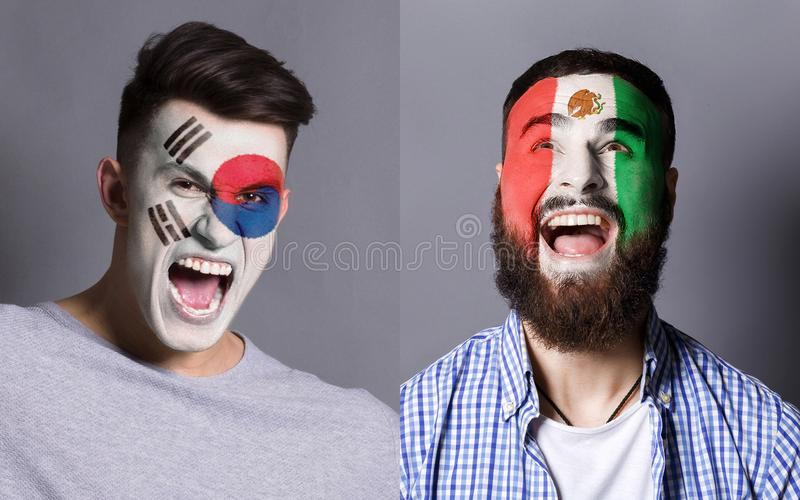 Emotional soccer fans with painted flags on faces. Emotional soccer fans with painted South Korea and Mexico flags on faces. Confrontation of football team stock images