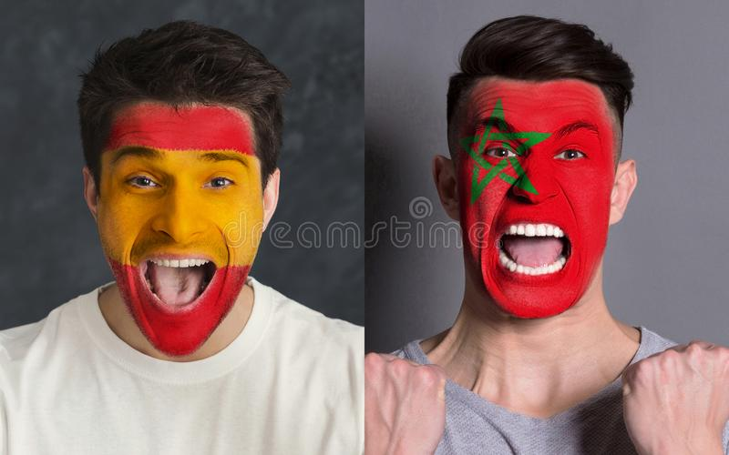 Emotional soccer fans with painted flags on faces. Emotional soccer fans with painted Spain and Morocco flags on faces. Confrontation of football team supporters stock photos