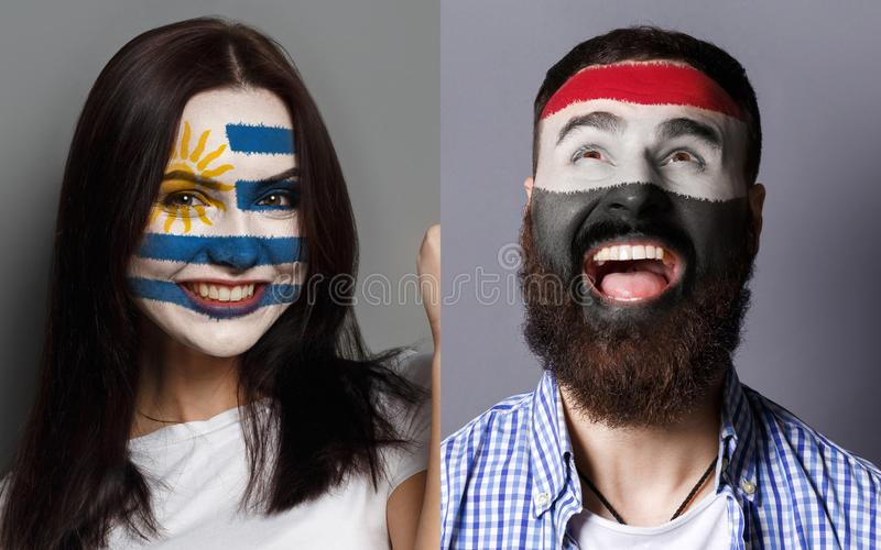 Emotional soccer fans with painted flags on faces. Emotional soccer fans with painted Uruguay and Egypt flags on faces. Confrontation of football team supporters stock image