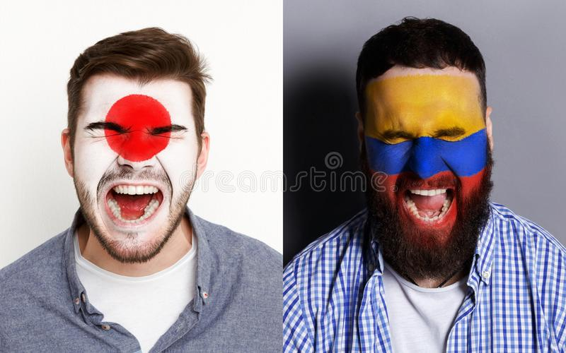 Emotional soccer fans with painted flags on faces. Emotional soccer fans with painted Japan and Colambia flags on faces. Confrontation of football team stock image