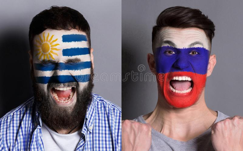 Emotional soccer fans with painted flags on faces. Emotional soccer fans with painted Uruguay and Russia flags on faces. Confrontation of football team royalty free stock image