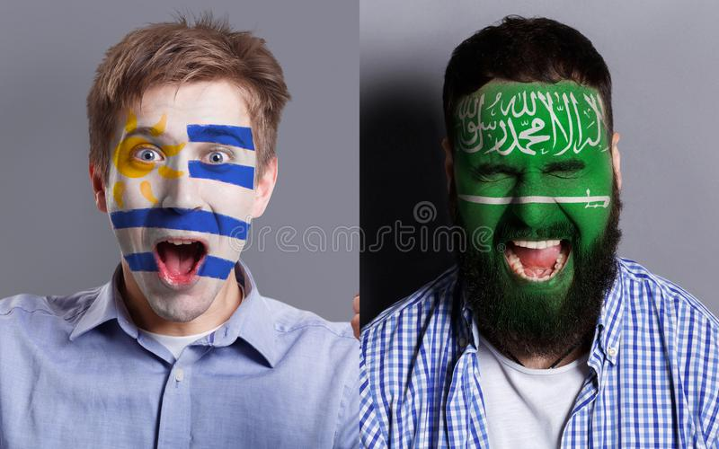Emotional soccer fans with painted flags on faces. Emotional soccer fans with painted Uruguay and Saudi Arabia flags on faces. Confrontation of football team royalty free stock photo