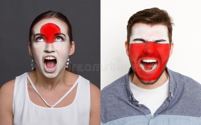 Emotional soccer fans with painted flags on faces. Emotional soccer fans with painted Japan and Poland flags on faces. Confrontation of football team supporters royalty free stock image