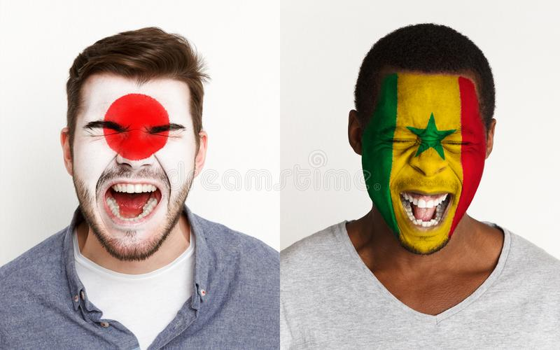 Emotional soccer fans with painted flags on faces. Emotional soccer fans with painted Japan and Senegal flags on faces. Confrontation of football team supporters royalty free stock images