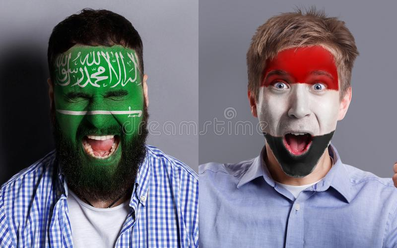 Emotional soccer fans with painted flags on faces. Emotional soccer fans with painted Saudi Arabia and Egypt flags on faces. Confrontation of football team stock image
