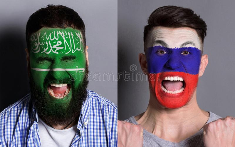 Emotional soccer fans with painted flags on faces. Emotional soccer fans with painted Saudi Arabia and Russia flags on faces. Confrontation of football team royalty free stock photos