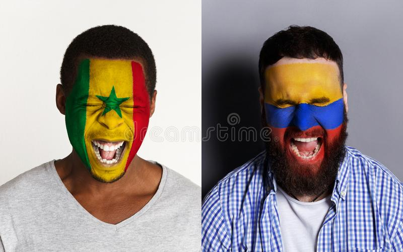 Emotional soccer fans with painted flags on faces. Emotional soccer fans with painted Senegal and Columbia flags on faces. Confrontation of football team stock photography