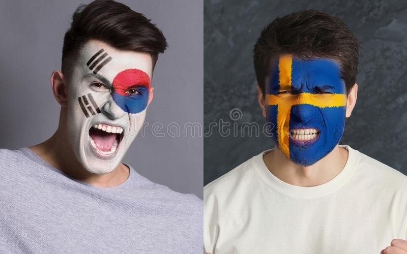 Emotional soccer fans with painted flags on faces. Emotional soccer fans with painted South Korea and Sweden flags on faces. Confrontation of football team stock photo