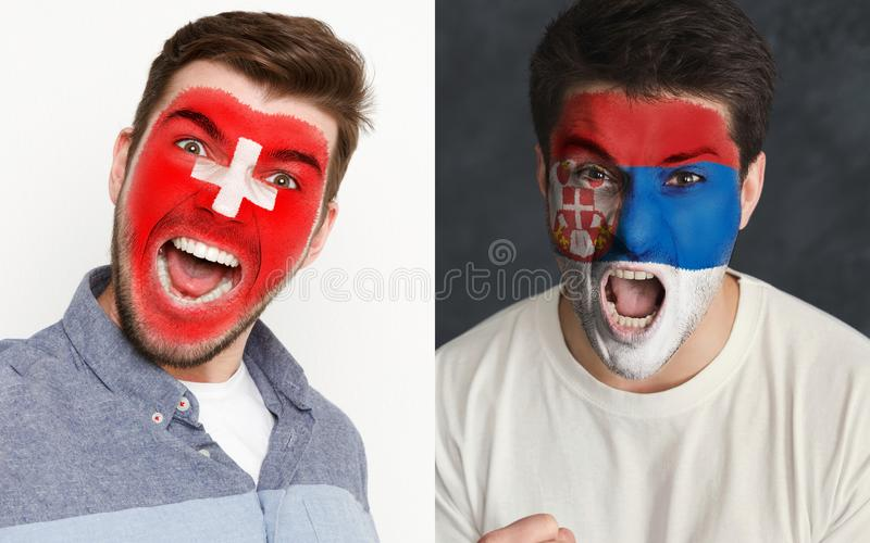 Emotional soccer fans with painted flags on faces. Emotional soccer fans with painted Switzerland and Serbia flags on faces. Confrontation of football team stock image