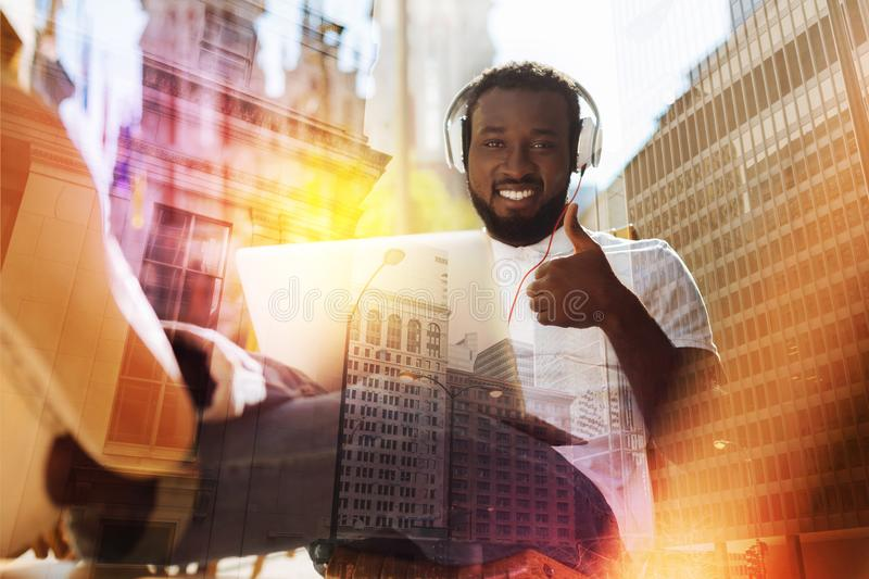 Emotional student showing his thumb while listening to music royalty free stock photos