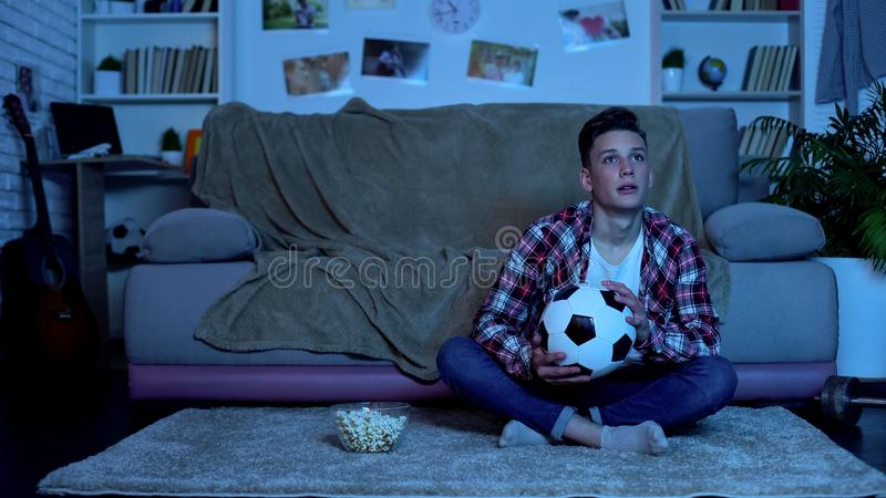 Emotional student watching soccer match on tv, national team winning game royalty free stock photos