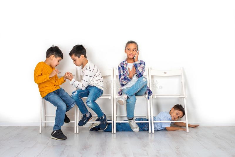 Emotional studio shot of children, girls and three boys sitting on chairs waiting. Older boys play armwrestling, the younger boy. Crawls on the floor and the stock photography