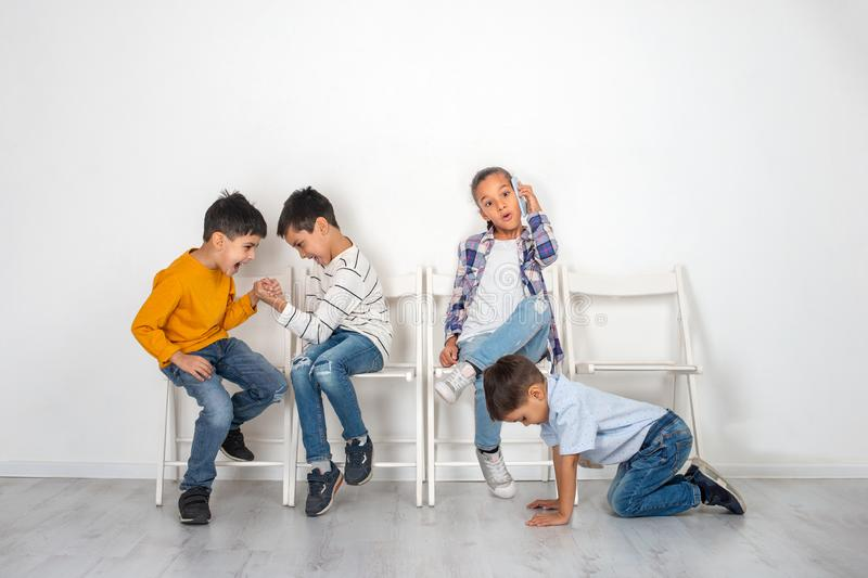 Emotional studio shot of children, girls and three boys sitting on chairs waiting. Older boys play armwrestling, the younger boy. Crawls on the floor and the stock image