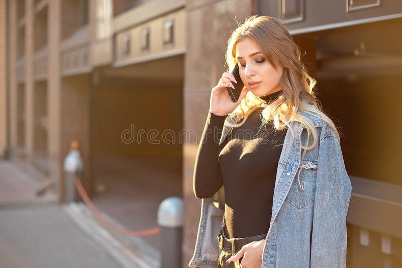 Emotional stylish portrait of a young blond woman on a cityscape background close-up in the setting sun. stock image