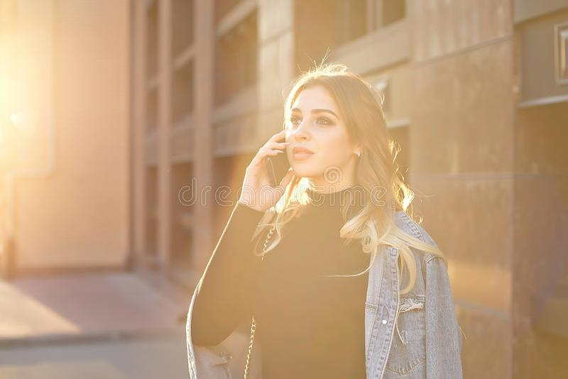 Emotional stylish portrait of a young blond woman on a cityscape background close-up in the setting sun. stock photography
