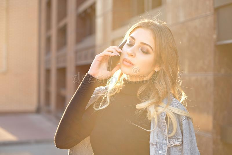Emotional stylish portrait of a young blond woman on a cityscape background close-up in the setting sun. stock photo