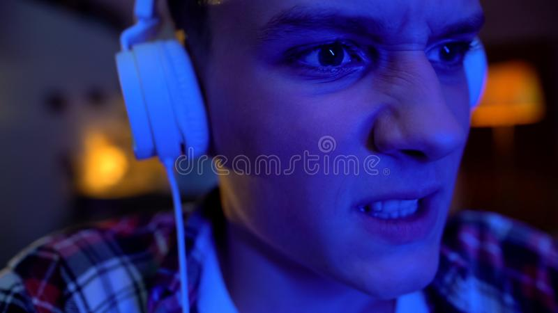 Emotional teenager playing video game night, awkward age, face mimics close-up royalty free stock image