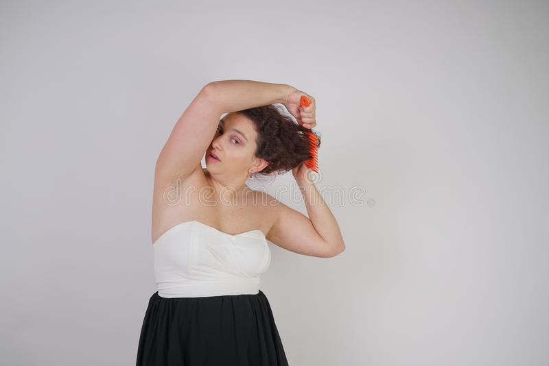 Emotional unhappy woman with disheveled hair tries to comb them and suffers. curvy girl stands on white background in Studio alone royalty free stock photography
