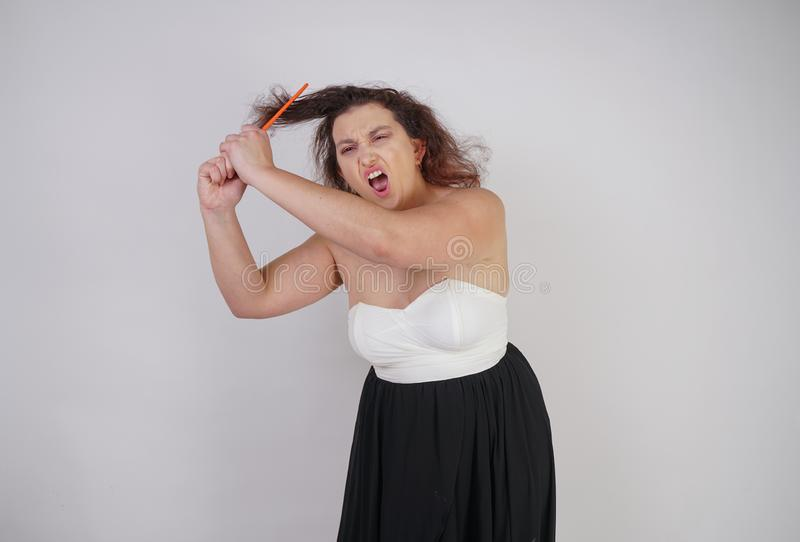 Emotional unhappy woman with disheveled hair tries to comb them and suffers. curvy girl stands on white background in Studio alone stock image