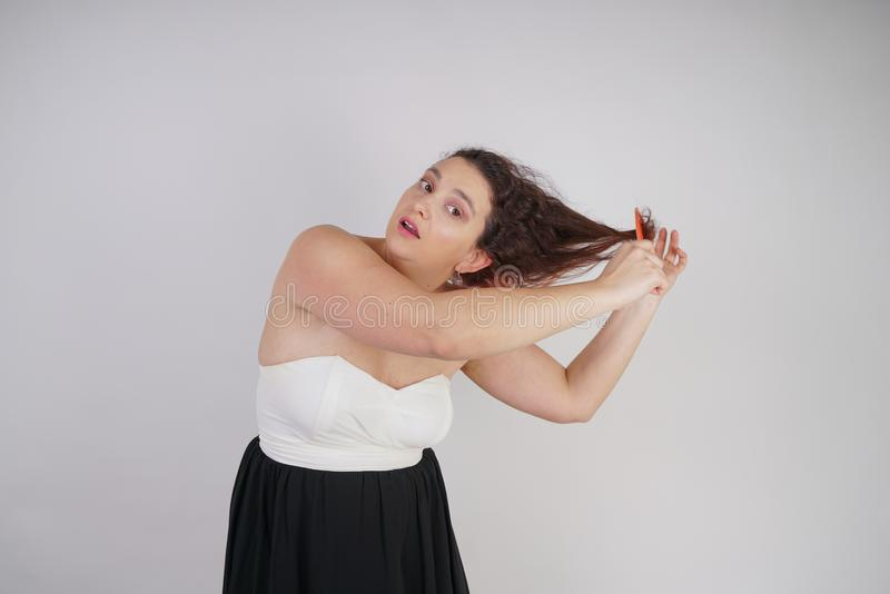 Emotional unhappy woman with disheveled hair tries to comb them and suffers. curvy girl stands on white background in Studio alone royalty free stock photos