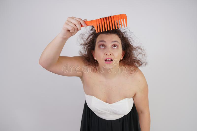 Emotional unhappy woman with disheveled hair tries to comb them and suffers. curvy girl stands on white background in Studio alone royalty free stock images