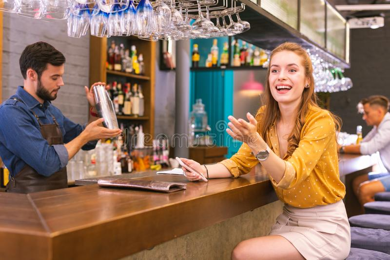 Emotional visitor of the bar smiling while noticing her friends. Sudden meeting. Cheerful young girl sitting at the bar counter and smiling while noticing her stock photos